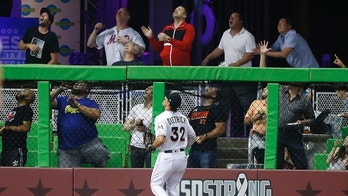Miami Marlins left fielder Derek Dietrich (32) and fans look on as a ball hit by New York Mets' Asdrubal Cabrera goes over the wall for a home run during the fourth inning of a baseball game, Tuesday, April 10, 2018, in Miami. (AP Photo/Wilfredo Lee)