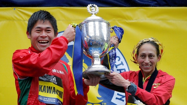 Yuki Kawauchi of Japan and Desiree Linden of the U.S. celebrate with the trophy after winning the men's and women's divisions of the 122nd Boston Marathon in Boston, Massachusetts, U.S., April 16, 2018.   REUTERS/Brian Snyder - RC1ABB5616D0