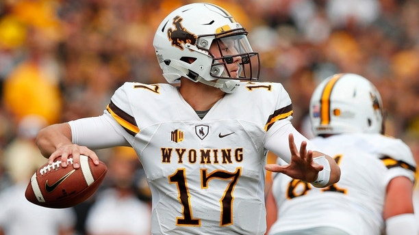 FILE - In this Sept. 2, 2017, file photo, Wyoming quarterback Josh Allen throws a pass during the first half of an NCAA college football game against Iowa, in Iowa City, Iowa. Four quarterbacks are certain to go in the first round of the NFL draft. (AP Photo/Charlie Neibergall, File)