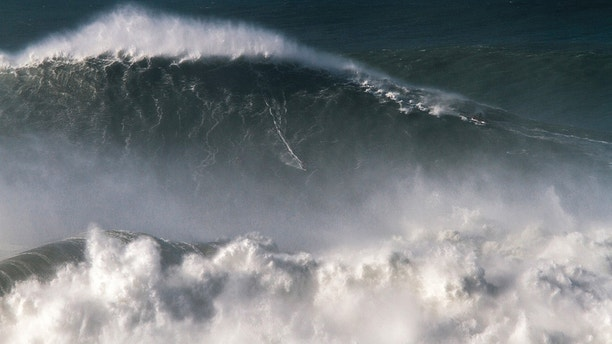 In this photo taken Nov. 8 2017, Brazilian surfer Rodrigo Koxa rides what has been judged the biggest wave ever surfed, at the Praia do Norte, or North beach, in Nazare, Portugal. On Saturday, April 28 2018, the World Surf League credited Koxa with a world record for riding the biggest wave ever surfed and said that its judging panel determined the wave was 80 feet (24.38 meters). (AP Photo/Pedro Cruz)