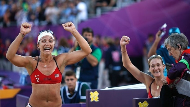 Misty May-Treanor (L) and Kerri Walsh Jennings of the U.S. celebrate defeating Italy's Greta Cicolari and Marta Menegatti during their women's quarterfinals beach volleyball match at Horse Guards Parade during the London 2012 Olympic Games August 5, 2012.           REUTERS/Marcelo del Pozo (BRITAIN  - Tags: OLYMPICS SPORT VOLLEYBALL TPX IMAGES OF THE DAY)   - LM2E8851G8T1R