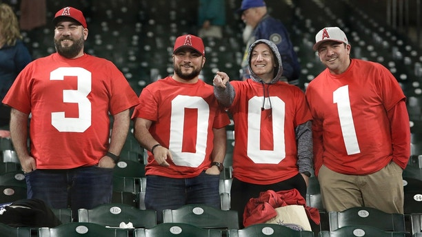Fans acknowledge Los Angeles Angels' Albert Pujols for reaching his 3,001th career hit following their baseball game against the Seattle Mariners Friday, May 4, 2018, in Seattle. (AP Photo/Jason Redmond)
