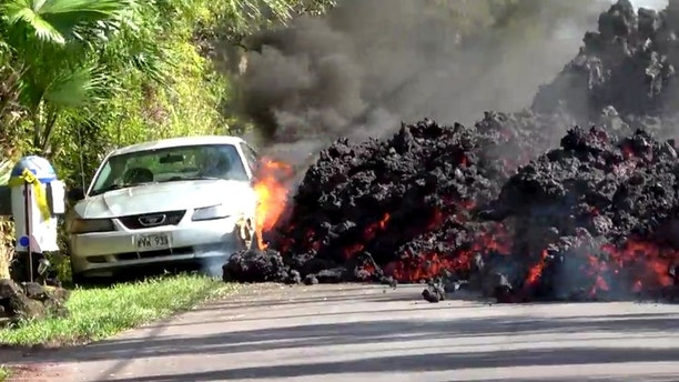 Lava engulfs a Ford Mustang in Puna, Hawaii, U.S., May 6, 2018 in this still image obtained from social media video. WXCHASING via REUTERS ATTENTION EDITORS - THIS IMAGE WAS PROVIDED BY A THIRD PARTY. NO RESALES. NO ARCHIVES. MANDATORY CREDIT: WXCHASING. NO NEW USES AFTER JUNE 5, 2018. UNITED STATES OUT. - RC143A361D90