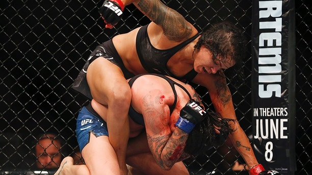 Amanda Nunes, top, from Brazil, top, fights Raquel Pennington, from the United States, during their UFC women's bantamweight mixed martial arts bout in Rio de Janeiro, Brazil, early Sunday, May 13, 2018. (AP Photo/Leo Correa)