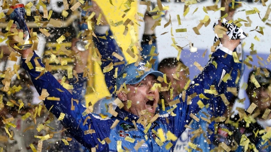 Kevin Harvick is covered in confetti as he celebrates winning the NASCAR Cup Series auto race at Kansas Speedway in Kansas City, Kan., Saturday, May 12, 2018. (AP Photo/Colin E. Braley)