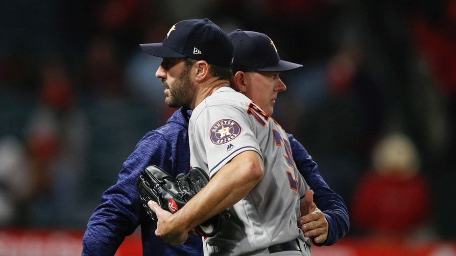 Houston Astros starting pitcher Justin Verlander gets a pack on the back from manager A.J. Hinch after the team's 2-0 win over the Los Angeles Angels in a baseball game Wednesday, May 16, 2018, in Anaheim, Calif.