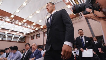 Nihon University's American football player Taisuke Miyagawa arrives for a news conference Tuesday, May 22, 2018, in Tokyo. The Japanese college football player has apologized for intentionally injuring the quarterback of an opposing team, an incident that has riveted Japan for several weeks.  In a news conference broadcast live across Japan, Miyagawa bowed deeply and said his coach had told him to do it - but he said he should have been stronger and refused the coaching order. (AP Photo/Eugene Hoshiko)