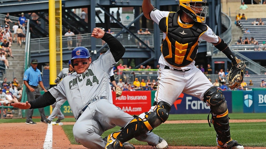 Pittsburgh Pirates catcher Elias Diaz, right, throws to first after getting the force-out at home plate on Chicago Cubs' Anthony Rizzo (44) on a fielder's choice to shortstop by Cub's Chris Gimenez in the eighth inning of a baseball game in Pittsburgh.