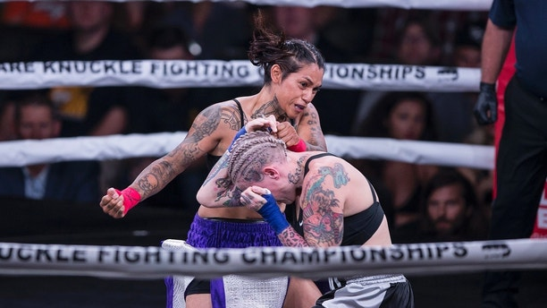 Alma Garcia, left, swings at Bec Rawlings during a 125-pound bout at the Bare Knuckle Fighting Championship at the Ice and Events Center on Saturday, June 2, 2018, in Cheyenne, Wyo. Rawlings won the bout. (AP Photo/Michael Smith)