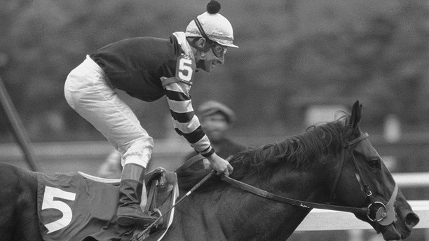 Jean Cruguet is smiling and up in the irons after taking Seattle Slew across the finish line to win the 109th running of the Belmont Stakes, and the Triple Crown, at Belmont Park in Elmont, N.Y., Saturday, June 11, 1977.   Seattle Slew led the race from the starting gate. AP Photo)