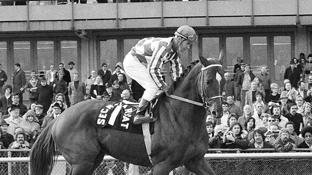 "Triple Crown winner Secretariat, with his usual jockey Ron Turcotte aboard, struts past the grandstand at Aqueduct Rack Track in New York, Nov. 6, 1973, as the three-year-old colt, nicknamed ""Super Red"" by his fans, made a final appearance before going to stud at Claiborne Farm in Kentucky. (AP Photo/Dave Pickoff)"
