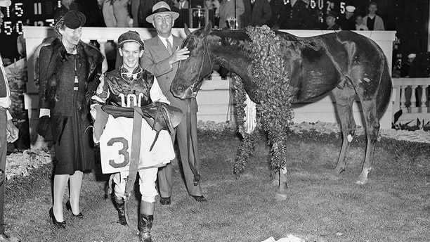 Wearing a garland of Roses, Assault stands in the Kentucky Derby winner?s circle, May 4, 1946 at Louisville, with (left to right) Mrs. Robert J. Kleberg, Jr.; Jockey Warren Mehrtens; and owner Robert J. Kleberg, Jr. of King Ranch, Texas. (AP Photo)