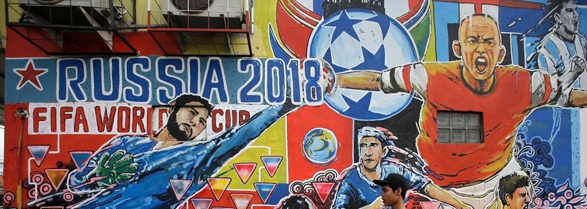 Boys walk past a mural of soccer players in action to advertise the upcoming the 2018 World Cup soccer tournament in Russia on the outskirts of Jakarta, Indonesia. Tuesday, June 12, 2018. (AP Photo/Tatan Syuflana)