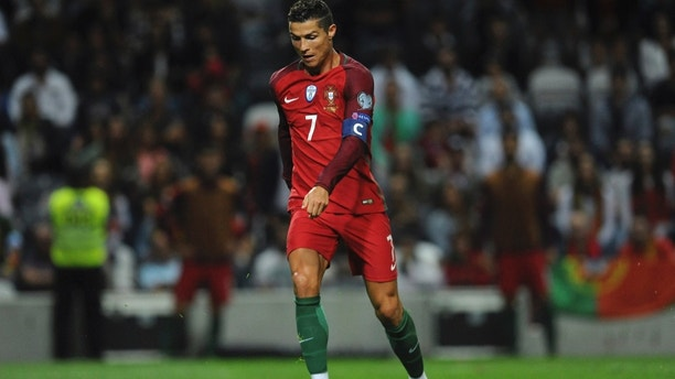 FILE - In this Thursday Aug. 31, 2017 filer, Portugal's Cristiano Ronaldo scores his side's fourth goal during the World Cup Group B qualifying soccer match between Portugal and Faroe Islands at the Bessa Stadium in Porto, Portugal. (AP Photo/Paulo Duarte, File)