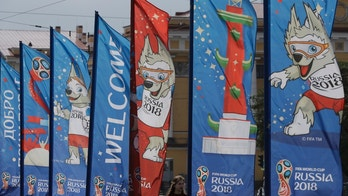 A woman walks past near the banners for the 2018 soccer World Cup in St. Petersburg, Russia, Tuesday, June 12, 2018. (AP Photo/Lee Jin-man)