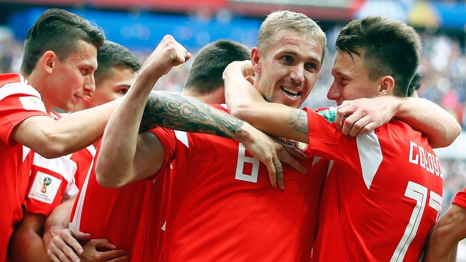 Russia's Yuri Gazinsky celebrates with teammates after scoring his side's first goal during the group A match between Russia and Saudi Arabia which opens the 2018 soccer World Cup at the Luzhniki stadium in Moscow, Russia.