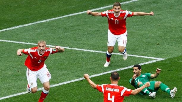 Russia's Yuri Gazinsky, left, celebrates scoring his side's first goal during the group A match against Saudi Arabia which opens the 2018 soccer World Cup at the Luzhniki stadium in Moscow, Russia, Thursday, June 14, 2018. (AP Photo/Victor Caivano)