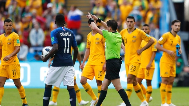 Referee Andres Cunha from Uruguay, centre, gestures for a penalty fro France after consulting VAR, from which France's Antoine Griezmann scored, during the group C match between France and Australia at the 2018 soccer World Cup in the Kazan Arena in Kazan, Russia, Saturday, June 16, 2018. France won the game 2-1, it was the first time in a World Cup that VAR has been used to award a penalty. (AP Photo/Pavel Golovkin)
