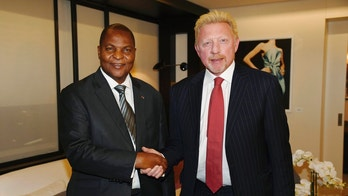 FILE - In this file photo originally released on Friday, April 27, 2018, President Prof. Faustin Archange Touadera, left, shakes hands with retired German tennis star Boris Becker in Brussels, Belgium, after it was announced Becker has been appointed by the Central African Republic as its Attache for Sports and Humanitarian and Cultural Affairs in the European Union with immediate effect. Lawyers for Becker claimed in Britain's High Court late Thursday June 14, 2018, that Becker's role as a sports attache for the Central African Republic gives him diplomatic immunity from bankruptcy proceedings.  (Irle Moser Rechtsanwalte PartG via AP Images, FILE)
