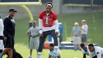 Carolina Panthers' Cam Newton (1) reacts as he jokes with players and coaches during the NFL football team's practice in Charlotte, N.C., Thursday, June 14, 2018. (AP Photo/Chuck Burton)