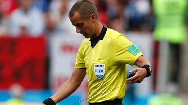 Referee Mark Geiger from the US adjusts his ear piece during the group B match between Portugal and Morocco at the 2018 soccer World Cup in the Luzhniki Stadium in Moscow, Russia, Wednesday, June 20, 2018. (AP Photo/Francisco Seco)