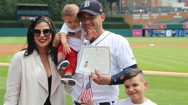 In a photo from June 25, 2018, Detroit Tigers shortstop Jose Iglesias poses with his wife Arlene and their children Alvaro, 9 months and Jose, 7, after becoming an American citizen during a naturalization ceremony before a baseball game, in Detroit. (AP Photo/Carlos Osorio)