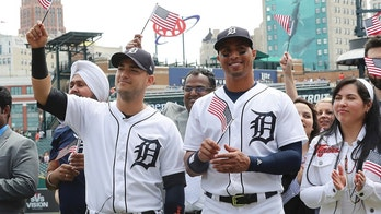 Detroit Tigers shortstop Jose Iglesias, left, and center fielder Leonys Martin wave an American flag after participating in a naturalization ceremony before a baseball game, Monday, June 25, 2018, in Detroit. (AP Photo/Carlos Osorio)