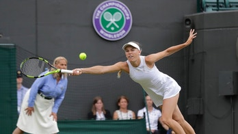 Caroline Wozniacki of Denmark returna a ball to Ekaterina Makarova of Russia during their women's singles match on the third day at the Wimbledon Tennis Championships in London, Wednesday July 4, 2018. (AP Photo/Ben Curtis)