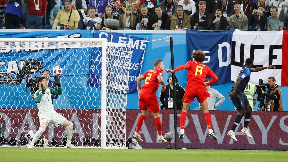 Samuel Umtiti, in blue, scores the only goal of the game bast Belgium's Thibault Courtois.