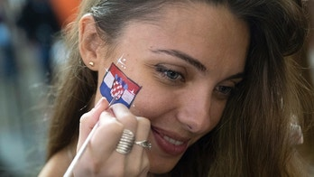 Russia's soccer fan is painted her face in Croatia's national flag after Croatia won the semifinal soccer match between Croatia and England during the 2018 soccer World Cup at the Luzhniki stadium, in Nikolskaya street near the Kremlin in Moscow, Russia, early Thursday, July 12, 2018. (AP Photo/Pavel Golovkin)