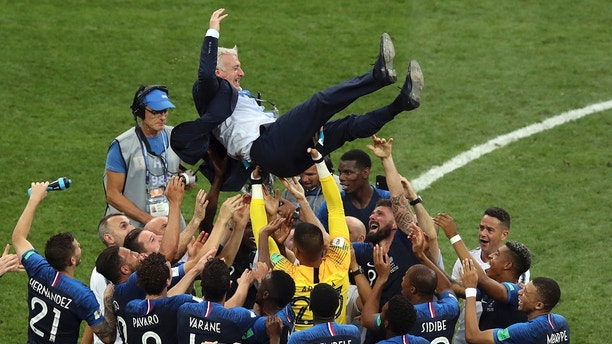 French players throw France head coach Didier Deschamps into the air celebrating at the end of the final match between France and Croatia at the 2018 soccer World Cup in the Luzhniki Stadium in Moscow, Russia, Sunday, July 15, 2018. (AP Photo/Thanassis Stavrakis)