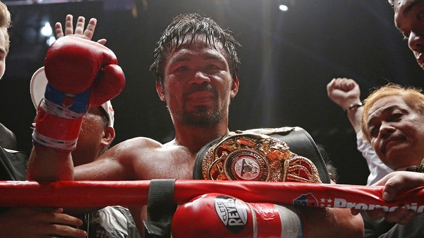 Manny Pacquiao of the Philippines poses after defeating Lucas Matthysse of Argentina during their WBA World welterweight title bout in Kuala Lumpur, Malaysia, Sunday, July 15, 2018. Pacquiao won the WBA welterweight world title after knocking out Matthysse on round seven. (AP Photo/Yam G-Jun)