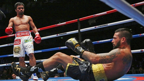 Lucas Matthysse, left, of Argentina falls after receiving a punch by Manny Pacquiao of the Philippines during their WBA World welterweight title bout in Kuala Lumpur, Malaysia, Sunday, July 15, 2018. Filipino boxing legend Pacquiao clinched his 60th victory Sunday with a seventh-round knockout of Matthysse, his first stoppage in nine years, that will help revive his career. (AP Photo/Yam G-Jun)