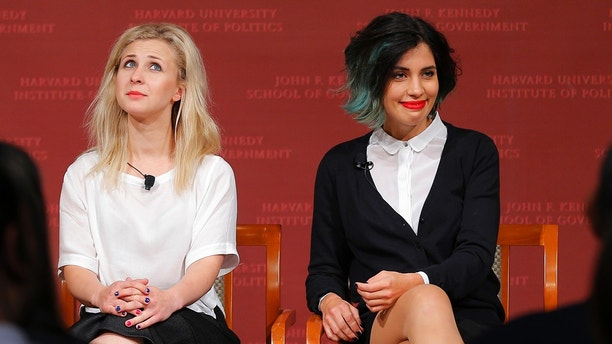 Maria Alyokhina (L) and Nadezhda Tolokonnikova, members of the punk protest band Pussy Riot, take their seats onstage for a forum at the Kennedy School of Government at Harvard University in Cambridge, Massachusetts September 15, 2014.    REUTERS/Brian Snyder (UNITED STATES - Tags: EDUCATION POLITICS SOCIETY) - GM1EA9G0L3G01