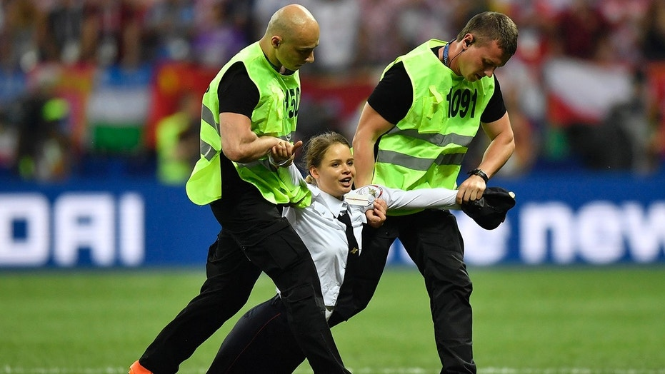 Stewards pull a woman off the pitch after she stormed onto the field and interrupted the final match between France and Croatia at the 2018 soccer World Cup in the Luzhniki Stadium.