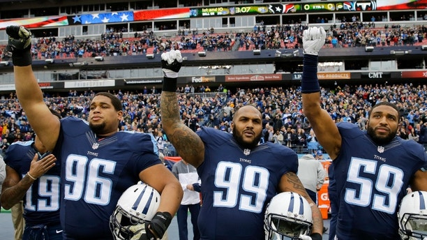 Tennessee Titans players Al Woods (96), Jurrell Casey (99), and Wesley Woodyard (59) raise their fists at the end of the national anthem before an NFL football game against the Houston Texans Sunday, Jan. 1, 2017, in Nashville, Tenn. (AP Photo/James Kenney)