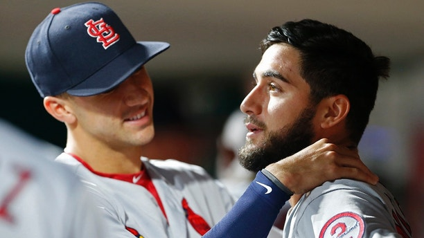 St. Louis Cardinals starting pitcher Daniel Poncedeleon, right, gets a hug in the dugout by Jack Flaherty, left, following seven no-hit innings against the Cincinnati Reds in a baseball game, Monday, July 23, 2018, in Cincinnati. (AP Photo/Gary Landers)
