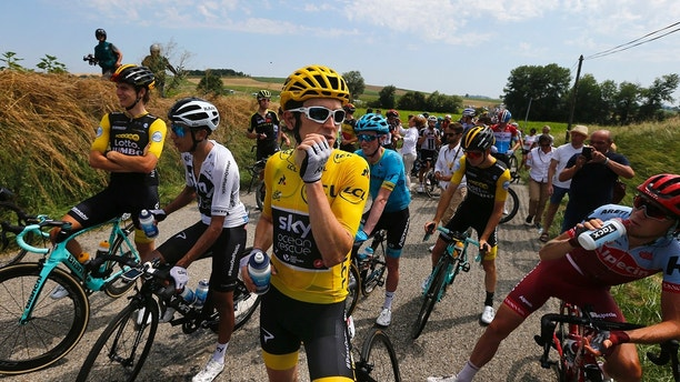 Riders with Britain's Geraint Thomas, wearing the overall leader's yellow jersey Britain's wait on the road after a farmer's protest interrupted the sixteenth stage of the Tour de France cycling race over 218 kilometers (135.5 miles) with start in Carcassonne and finish in Bagneres-de-Luchon, France, , Tuesday, July 24, 2018. (AP Photo/Peter Dejong)