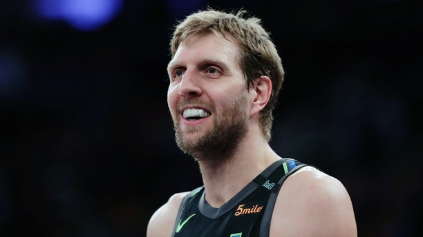 FILE - In this March 13, 2018, file photo, Dallas Mavericks' Dirk Nowitzki smiles during the second half of an NBA basketball game against the New York Knicks, in New York. Dirk Nowitzki is officially signed for a record 21st season with the Dallas Mavericks. The Mavericks announced Monday, July 23, 2018, that they had re-signed the 13-time All-Star. (AP Photo/Frank Franklin II)