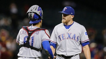 Texas Rangers pitcher Jake Diekman and Robinson Chirinos (61) celebrate after defeating the Arizona Diamondbacks 9-5 during a baseball game, Monday, July 30, 2018, in Phoenix. (AP Photo/Rick Scuteri)