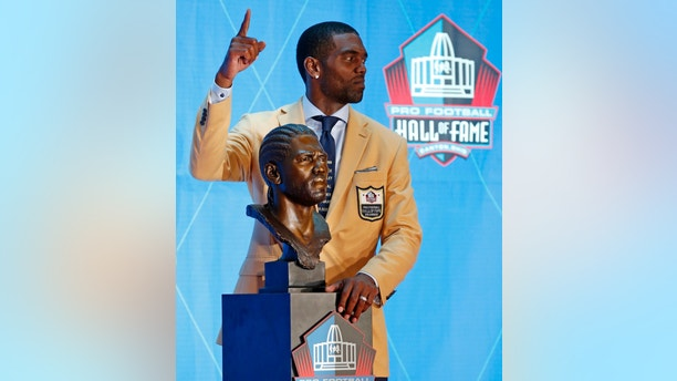 Former NFL wide receiver Randy Moss poses with a bust of himself during inductions at the Pro Football Hall of Fame, Saturday, Aug. 4, 2018 in Canton, Ohio. (AP Photo/Ron Schwane)