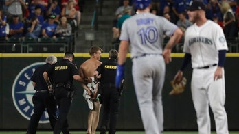 Toronto Blue Jays' Brandon Drury (10) stands on second base as a man who jumped out of the stands and ran naked in the Safeco Field outfield is taken away by sheriff's deputies during the ninth inning of the Blue Jays' baseball game against the Seattle Mariners, Saturday, Aug. 4, 2018, in Seattle. (AP Photo/Ted S. Warren)