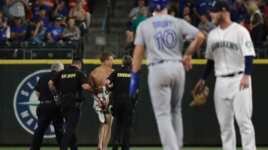 Toronto Blue Jays' Brandon Drury stands on second base as a man who jumped out of the stands and ran naked in the Safeco Field outfield is taken away by sheriff's deputies.