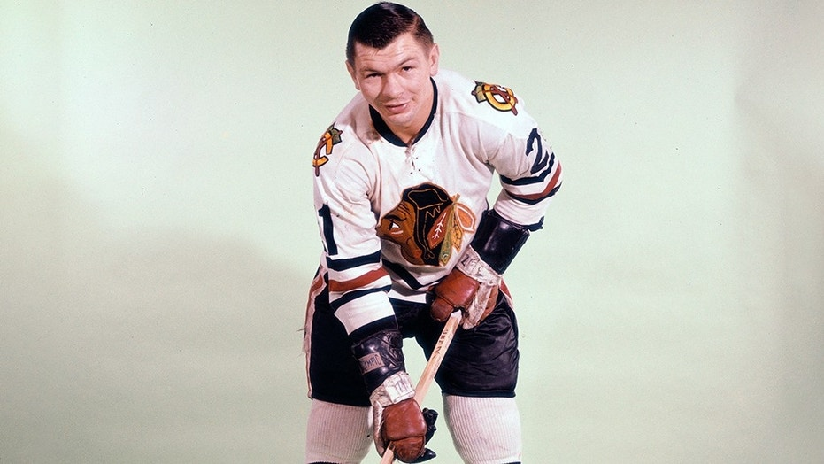 Stan Mikita (21) holds the Stanley Cup at a 1996 ceremony honoring the Blackhawks' 1961 championship team.