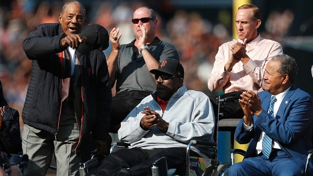 Former San Francisco Giants players Willie Mays, Will Clark, Kirk Rueter, Juan Marichal and Willie McCovey, clockwise from left, acknowledge fans during a ceremony to retire Barry Bonds' jersey number before a baseball game between the Giants and the Pittsburgh Pirates in San Francisco, Saturday, Aug. 11, 2018. (John G. Mabanglo/Pool Photo via AP)