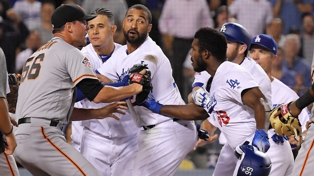 San Francisco Giants relief pitcher Tony Watson, left, scuffles with Los Angeles Dodgers' Yasiel Puig, right, as other members of the Dodgers get involved after Puig shoved Giants catcher Nick Hundley during the seventh inning of a baseball game, Tuesday, Aug. 14, 2018, in Los Angeles. (AP Photo/Mark J. Terrill)