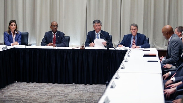 Ohio State University board of trustees member Abigail Wexner, left, university president Dr. Michael Drake, board secretary and senior advisor Jeff Kaplan, right, listen as board chair Michael Gasser reads a statement during a meeting of Ohio State University trustees to discuss the future of NCAA college football coach Urban Meyer in Columbus, Ohio, Wednesday, Aug. 22, 2018. The board will meet in private to decide whether the superstar coach should be punished for the way he handled domestic-abuse allegations against a former assistant. (AP Photo/Paul Vernon)