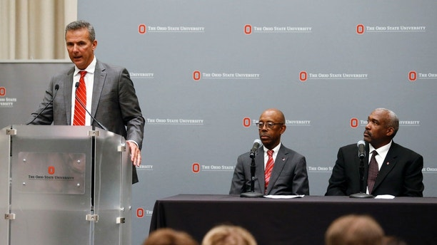 Ohio State football coach Urban Meyer, left, makes a statement during a news conference as university President Michael Drake, center, and athletic director Gene Smith listen in Columbus, Ohio, Wednesday, Aug. 22, 2018. Ohio State suspended Meyer on Wednesday for three games for mishandling domestic violence accusations, punishing one of the sport's most prominent leaders for keeping an assistant on staff for several years after the coach's wife accused him of abuse. Gene Smith was suspended from Aug. 31 through Sept. 16. (AP Photo/Paul Vernon)