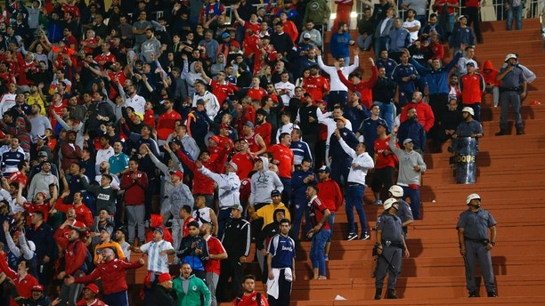 Police stand next to fans of Argentina's Independiente at the end of a Copa Libertadores soccer match against Brazil's Santos, in Sao Paulo, Brazil, Tuesday, Aug. 28, 2018. Independent won 3-0 on aggregate. (AP Photo/Andre Penner)