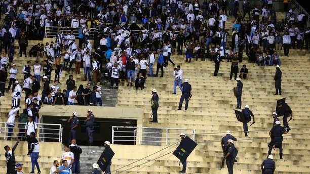 Police order the fans of Brazil's Santos to leave the grandstand after fights broke out in the stands at the end of a Copa Libertadores soccer match with Argentina's Independiente, in Sao Paulo, Brazil, Tuesday, Aug. 28, 2018. Independent won 3-0 on aggregate. (AP Photo/Andre Penner)